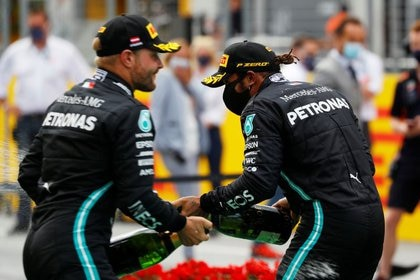 Fórmula Uno F1 - Gran Premio de Steiermark - Red Bull Ring, Spielberg, Styria, Austria - 12 de julio de 2020. Lewis Hamilton de Mercedes (derecha) lleva una mascarilla mientras celebra después de ganar la carrera, con el segundo puesto de Mercedes, Valtteri Bottas, tras la reanudación de la F1 después del brote de la enfermedad coronavirus (COVID-19) REUTERS/Leonhard Foeger/Pool