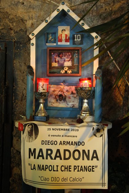 """A shrine with the inscription """"Maradona has passed away on November 25, 2020. Napoli is crying, Goodbye to the God of Football"""" at the so-called """"Maradona Corner"""" at the top of the Quartieri Spagnoli in Naples on November 25, 2020 after the annoucement's of Argentinian football legend Diego Maradona's death. - Argentine football legend Diego Maradona has died at the age of 60, his spokesman announced November 25, 2020. (Photo by Carlo Hermann / AFP)"""
