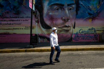 Un hombre con un tapabocas camina frente a un graffiti de Simón Bolívar, en una calle de Caracas (Venezuela). EFE/Miguel Gutiérrez/Archivo