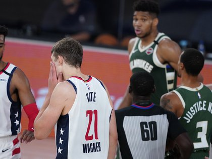 Aug 11, 2020; Lake Buena Vista, Florida, USA; Washington Wizards' Moritz Wagner (21) grabs his face after getting head butted by Milwaukee Bucks' Giannis Antetokounmpo, rear, during the first half of an NBA basketball game, Tuesday, Aug. 11, 2020, in Lake Buena Vista, Fla. at Visa Athletic Center.  Antetokounmpo was ejected from the game. Mandatory Credit: Ashley Landis/Pool Photo-USA TODAY Sports