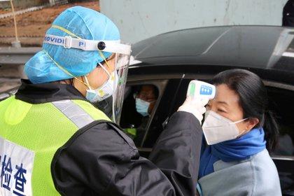 Un oficial de seguridad chequea la temperatura de un pasajero en Xianning, cerca de Wuhan  (REUTERS/Martin Pollard)