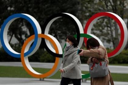 Los peatones con mascarillas caminan por los anillos olímpicos frente al Museo Olímpico de Japón, en Tokio, Japón, el 30 de marzo de 2020. REUTERS/Issei Kato