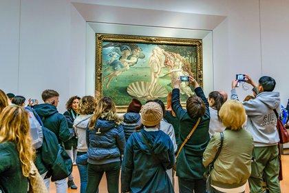 """Personas tomando fotos de la famosa """"Venus"""" de Botticelli en la Galería de los Uffizi en la ciudad de Florencia, Italia"""