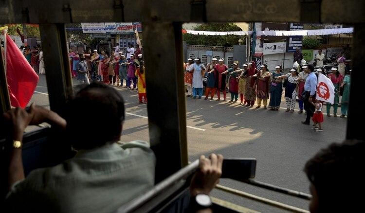 """Activistas levantan el puño y juran proteger sus derechos mientras forman un """"muro de las mujeres"""", que llegó a tener cientos de kilómetros de largo (AP)"""