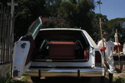 Trabajadores se disponen a bajar un ataúd con una víctima de COVID-19 de un vehículo para proceder a enterrarlo en San Cristóbal (Venezuela). EFE/ Johnny Parra/Archivo