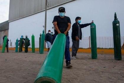 Las filas para recargar los tanques de oxígeno, un elemento escaso para el tratamiento de pacientes (Reuters)