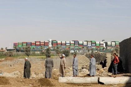 Personas observan el barco navegando otra vez por el Canal de Suez (REUTERS/Mohamed Abd El Ghany)