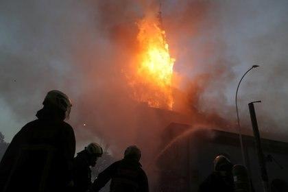 Los bomberos trabajan en el sitio de una iglesia que fue incendiada durante una protesta contra el gobierno de Chile, en el primer aniversario de las protestas y disturbios que sacudieron la capital en 2019, en Santiago, Chile. REUTERS/Ivan Alvarado