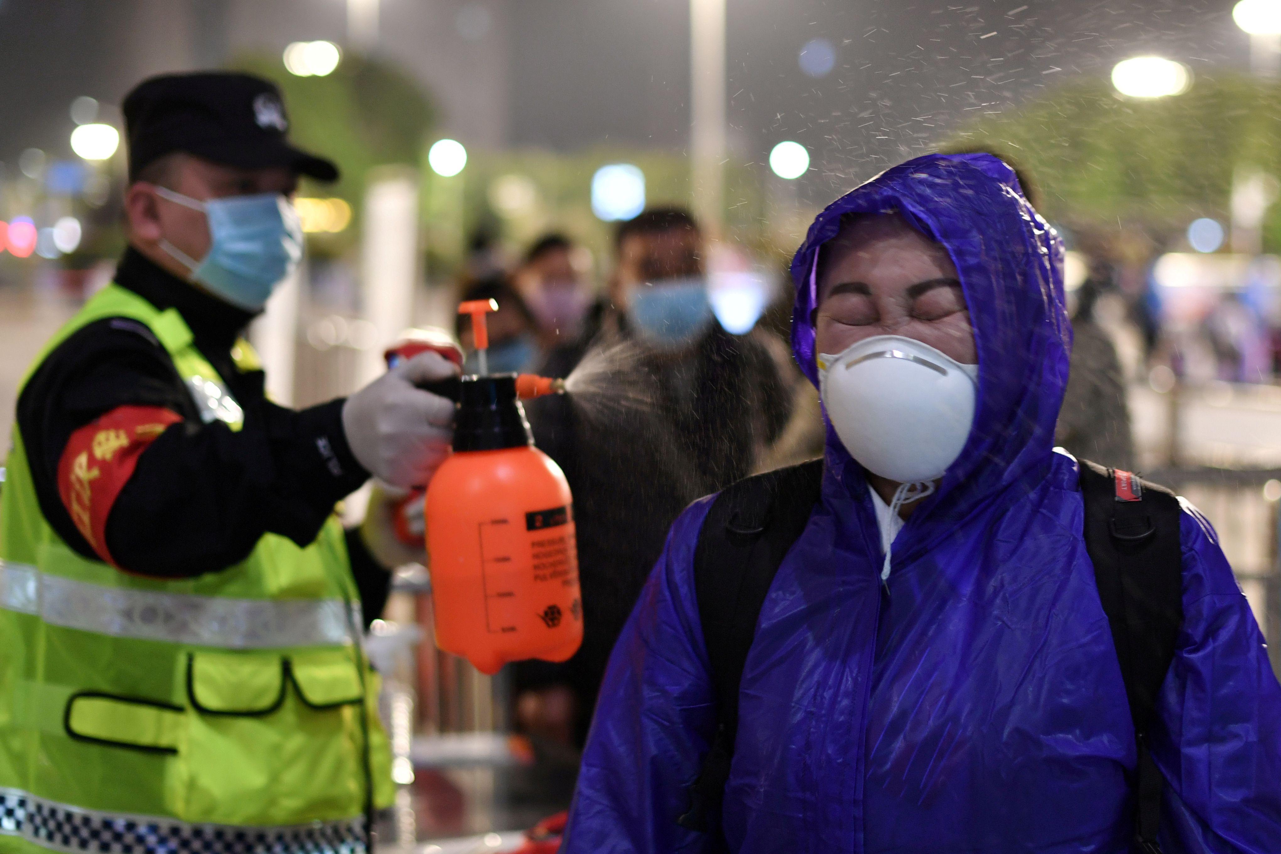 Un oficial de policía rocía desinfectante a una pasajera fuera de la estación de tren de Hankou después de que se levantaran las restricciones de viaje para abandonar Wuhan, la capital de la provincia de Hubei y el epicentro del nuevo brote de la enfermedad por coronavirus (Reuters)