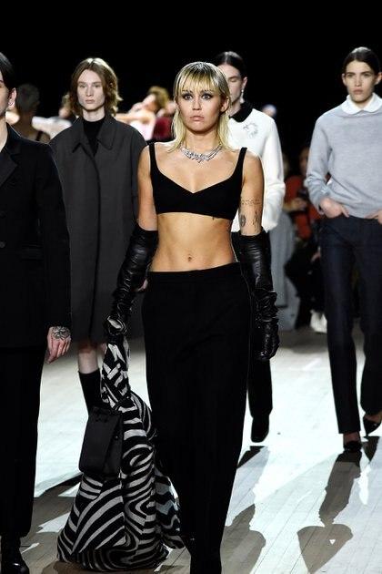Como broche de oro, una de las grandes invitadas al show, fue Miley Cyrus que lució un conjunto de dos piezas en negro. Top triangulito y pantalón sastrero tiro bajo. Como complementos, un saco con estampado de animal print de cebra y una cartera rectangular