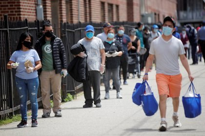 The people are waiting in a queue at a food bank at the Church of St. Martin, during an outbreak of the coronavirus in the section of Elmhurst, Queens, New York, (Reuters)