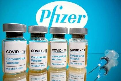 """Los frascos con una inscripción que dice """"COVID-19 / Vacuna contra el Coronavirus / Sólo inyección"""" y una jeringa médica se ven frente al logo de Pfizer en esta ilustración tomada el 31 de octubre de 2020 (REUTERS/Dado Ruvic)"""