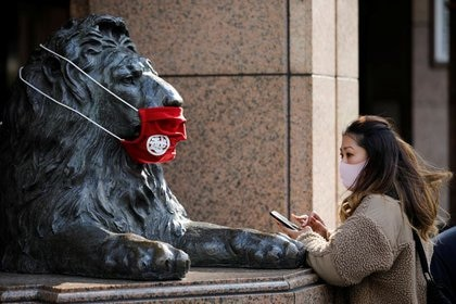 Una mujer usando una mascarilla frente a una estatua, también con mascarilla, en Tokio (REUTERS/Kim Kyung-Hoon)