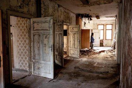 Una mujer, parada en el interior de una villa abandonada construida en 1900 cerca de Eisenach, en el este de Alemania, el 21 de septiembre de 2020.  (AP Foto/Michael Probst)