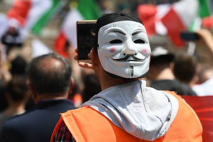 """Un """"chaleco naranja"""" con una máscara de Guy Fawkes durante la manifestación de este martes en Roma. (Vincenzo PINTO / AFP)"""