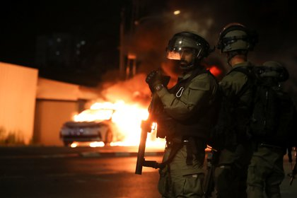 Miembros de las fuerzas de seguridad israelíes permanecen cerca de un coche de policía israelí en llamas durante los enfrentamientos entre la policía israelí y miembros de la minoría árabe del país en la ciudad árabe-judía de Lod, Israel 12 de mayo de 2021. REUTERS/Ammar Awad