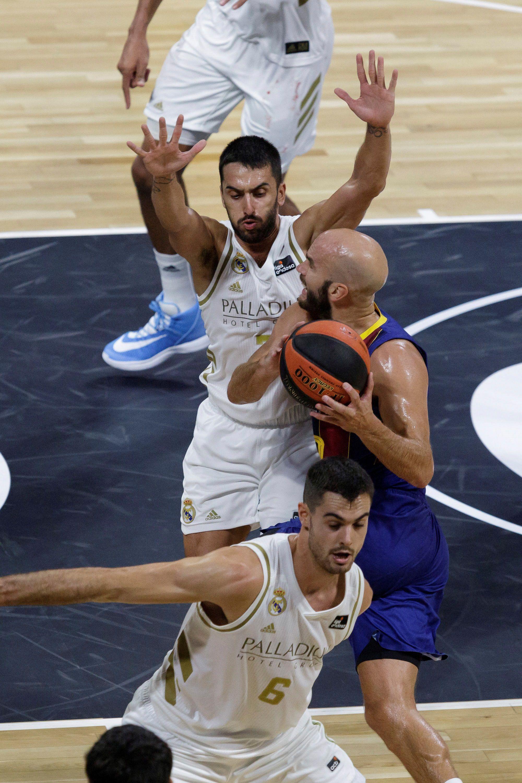 El base argentino del Real Madrid, Facundo Campazzo (detrás), defiende a Nick Calathes (c), base estadounidense del Barça, durante el partido correspondiente a la final de la Supercopa de baloncesto de la liga ACB disputado en el pabellón Santiago Martín de La Laguna (Tenerife). EFE/Ramón de la Rocha