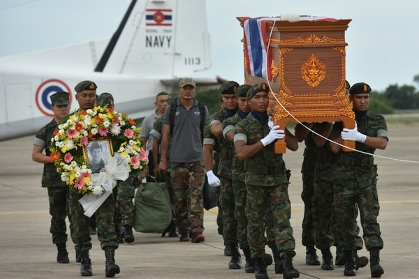An honour guard carries the coffin of Samarn Kunan, 38, a former member of Thailand's elite navy SEAL unit who died working to save 12 boys and their soccer coach trapped inside a flooded cave, at an airport in Rayong province, Thailand, July 6, 2018. REUTERS/Panumas Sanguanwong