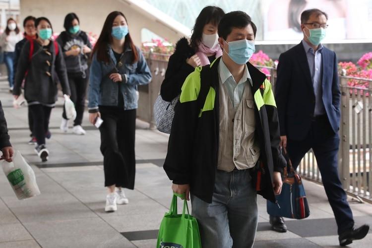 Varias personas utilizan máscaras mientras cruzan un puente en Hong Kong, el viernes 24 de enero de 2020, como medida preventiva frente a un brote de coronavirus que afecta a China. (AP Foto/Achmad Ibrahim)