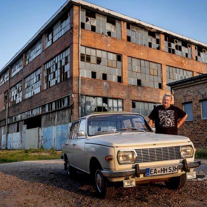 Wolfgang Hofmann posa junto a su auto Wartburg, construido en 1974, delante del edificio abandonado de la fábrica VEB de Alemania del Este, donde se construían autos BMW y Wartburg, en el este de Alemania, el 22 de septiembre de 2020. La planta cerró en 1991. Treinta años después de la reunificación de Alemania el 3 de octubre de 1990, muchas de las que en su día fueron decrépitas ciudades del este comunista han sido cuidadosamente restauradas y han surgido nuevas fábricas. Pero muchas empresas e instalaciones no sobrevivieron a la abrupta transición al capitalismo y las ineficientes empresas comunistas enfrentaron problemas para competir en una economía de mercado, mientras que la demanda de productos del este se desplomó y sus obsoletas factorías cerraron. (AP Foto/Michael Probst)