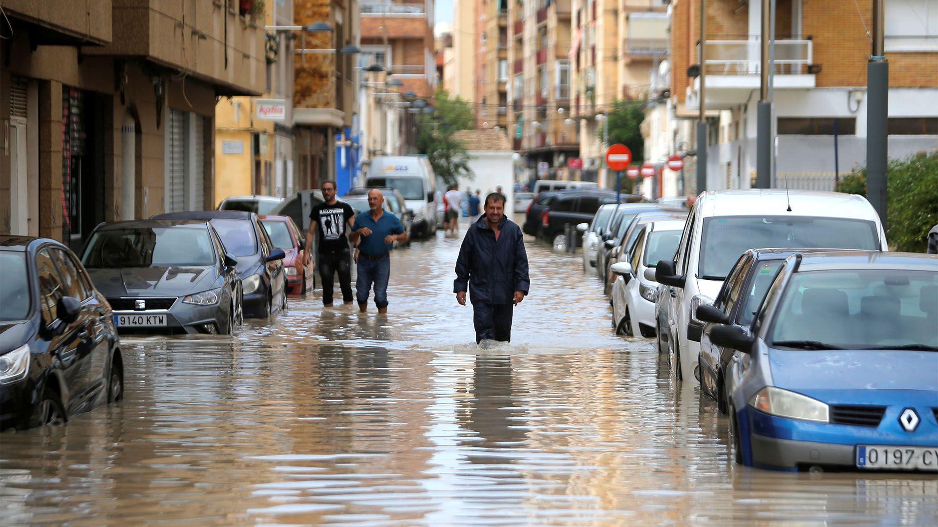 La gente camina por una calle inundada mientras las lluvias torrenciales azotan Orihuela, España, el 13 de septiembre de 2019 (REUTERS/Jon Nazca)