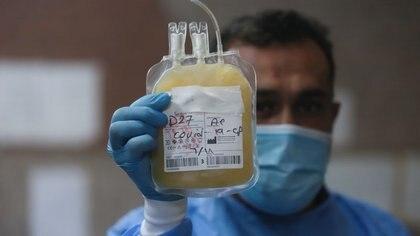 Un enfermero con mascarilla y guantes muestra plasma sanguíneo de una persona que se recuperó del COVID-19, la enfermedad causada por el coronavirus, que será utilizado en pacientes críticos, en un banco de sangre en Basora, Irak. 20 de junio, 2020. REUTERS/Essam Al-Sudani