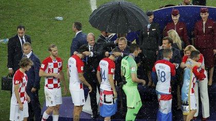 Un hombre protege a Putin de la lluvia mientras el resto se empapa (Reuters)