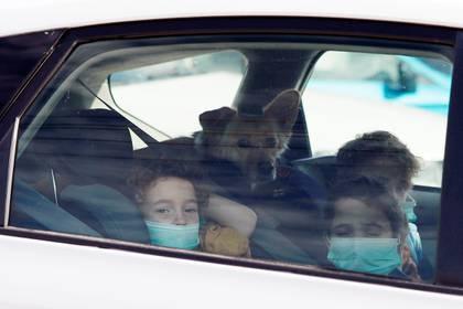 Menores permanecen dentro de un automóvil en la ciudad de Haifa, Israel, con sus barbijos puestos.  REUTERS/Ammar Awad