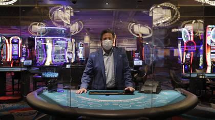 Bill Hornbuckle, CEO de MGM Resorts International, posa tras los acrílicos instalados en la mesa de blackjack en el hotel Bellagio (AP)