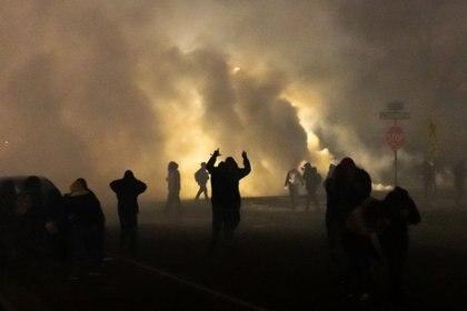 La gente se pone a cubierto mientras la policía dispara gases lacrimógenos frente a la estación de policía del Brooklyn Center durante una protesta después de que un oficial de policía disparó y mató a un hombre negro en el Brooklyn Center, Minneapolis, Minnesota, el 11 de abril de 2021. (Photo by Kerem Yucel / AFP)