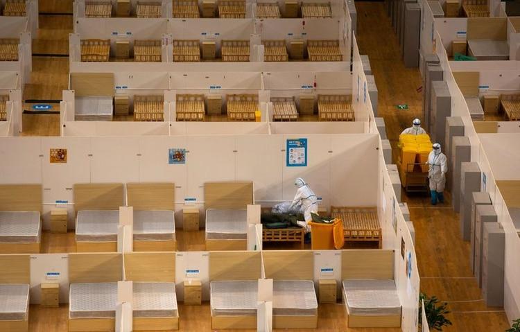 Trabajadores en trajes protectores limpian las habitaciones de un hospital improvisado que fue cerrado después de que el último grupo de pacientes con coronavirus haya sido dado de alta, en Wuhan, el epicentro del brote de coronavirus, en la provincia de Hubei, China, el 8 de marzo de 2020. China Daily vía REUTERS