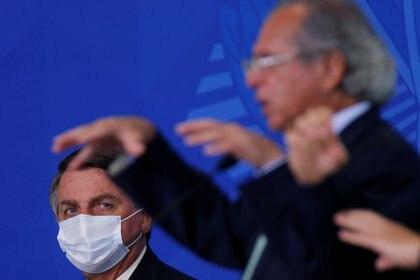 Bolsonaro mira al ministro de Economía, Paulo Guedes, durante una ceremonia de lanzamiento de un programa para ampliar el acceso al crédito en el Palacio del Planalto en Brasilia, el 19 de agosto de 2020. (REUTERS/Adriano Machado)