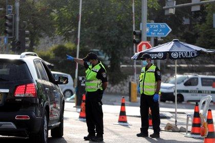 La policía israelí revisa un automóvil en un puesto de control después de que Israel ingresó a un segundo bloqueo nacional en medio de un resurgimiento de nuevos casos de enfermedad por coronavirus (COVID-19), lo que obligó a los residentes a permanecer principalmente en casa durante el pico de la temporada. de las fiestas judías a la entrada de Jerusalén.  REUTERS / Ronen Zvulun