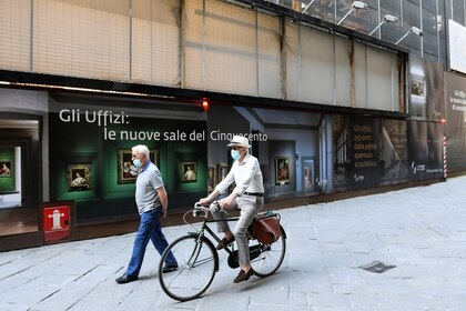 Un hombre con una máscara facial monta una bicicleta junto a otra caminando junto a una pancarta de la Galería de los Uffizi el día de su reapertura con nuevas reglas de distanciamiento social e higiene en vigor después de meses de cierre debido al brote de la enfermedad coronavirus (COVID-19), en Florencia, Italia, el 2 de junio de 2020. REUTERS/Jennifer Lorenzini