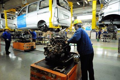 Empleados trabajan en una fábrica de ensamblaje de minivans en Qingdao (China). EFE/YU FANGPING/Archivo
