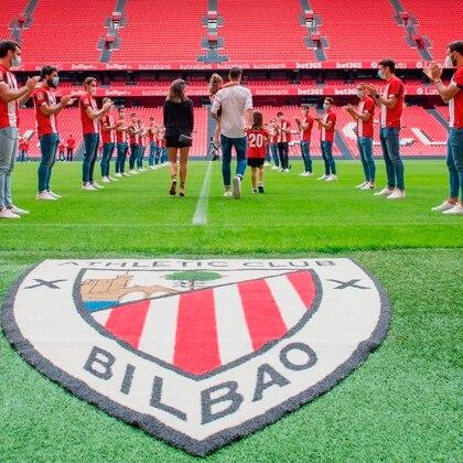 El jugador del Athletic de Bilbao, Aritz Aduriz, junto a su mujer y sus hijas en el pasillo de honor este viernes, en la despedida realizada por el club bilbaíno en San Mames, tras anunciar su retirada del fútbol en activo. EFE/ATHLETIC CLUB