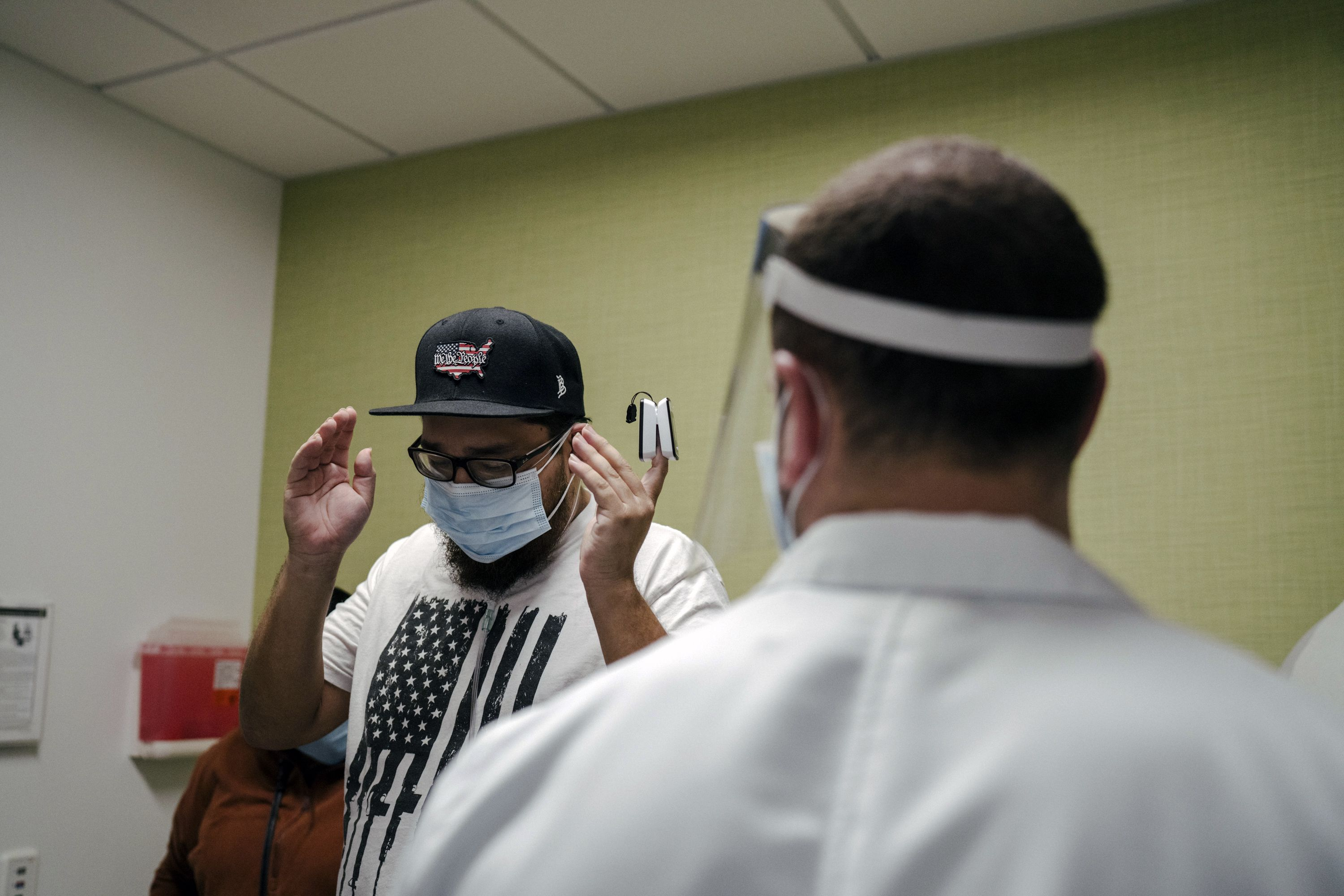 Gilbert Torres, left, returns to Martin Luther King Jr. Community Hospital in Los Angeles, where he had been on a ventilator in the intensive care unit, on Feb. 9, 2021. The hospital has created a new outpatient clinic for COVID-19 survivors, intended to address their lingering physical and psychic wounds — and to help keep them from needing to be readmitted. (Isadora Kosofsky/The New York Times)