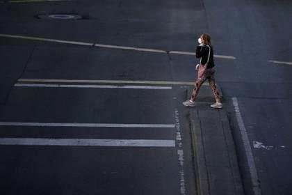 Una mujer con una máscara facial camina por una calle durante la hora pico, después de que el gobierno permitió que ciertos sectores volvieran a trabajar, en medio del brote de coronavirus en Bogotá (Reuters)