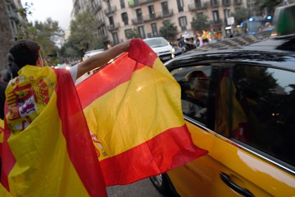 Un manifestante muestra la bandera de España durante una manifestación en favor de la unidad en Barcelona el pasado 4 de octubre (AFP)
