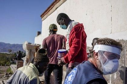 Miembros de la ONG Médicos del Mundo distribuyen alimentos a migrantes de Malí en San Isidro, durante el brote de la enfermedad por coronavirus (COVID-19) en Níjar, en la región de Almería, España, 29 abril 2020 (REUTERS/Juan Medina)