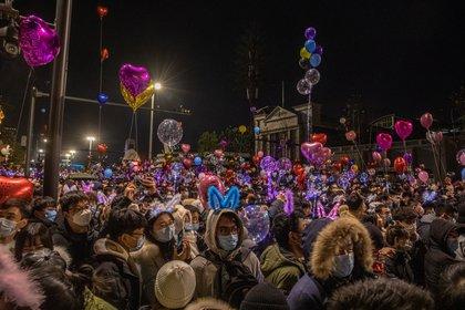 La gente se agolpa en la calle para celebrar el la llegada del nuevo año en Wuhan (EFE/EPA/ROMAN PILIPEY)