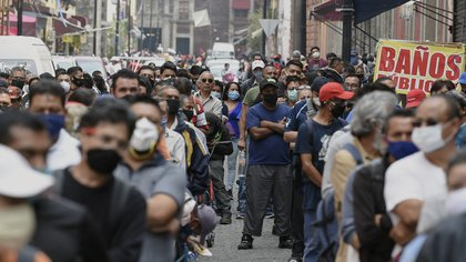 People queue in a street waiting to pass through a pedestrian control that limits the access in groups of 20 people to enter downtown Mexico City on July 6, 2020. - Mexico authorized the reopening of restaurants, shops, street markets and sport complexes but with limited capacity and hours amid the COVID-19 novel coronavirus pandemic. (Photo by ALFREDO ESTRELLA / AFP)