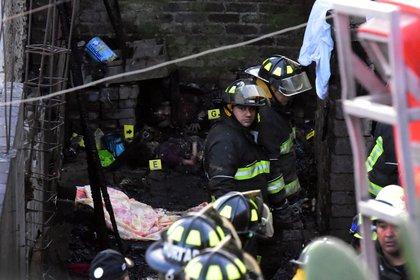 Bomberos trabajan en la escena de un incendio en el que siete niños murieron quemados en Iztalapala al este de la Ciudad de México el 28 de diciembre de 2018. (Foto por DANI ALPIDE / AFP)