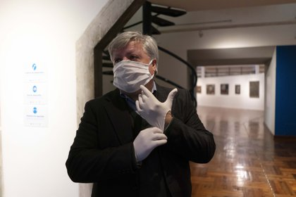 Wearing a face mask and plastic gloves amid the spread of new coronavirus, Enrique Aguerre, director of the National Museum of Visual Arts, waits for visitors on the second-day of reopening the museum in Montevideo, Uruguay, Tuesday, Aug. 4, 2020. After more than four months closed due to restrictions to curb the spread of COVID-19, movie houses, museums and theaters re-opened nationwide on Monday, with social distancing protocols. (AP Photo/Matilde Campodonico)