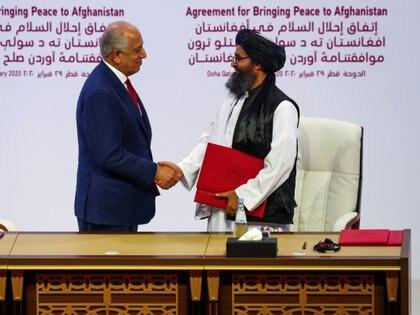 Mulá Abdul Ghani Baradar, el líder de la delegación talibán y Zalmay Khalilzad el enviado estadounidense para las negociaciones de paz, luego de rubricar el acuerdo. Foto:  REUTERS/Ibraheem al Omari