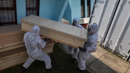 Trabajadores de una funeraria descargan un ataúd que contiene los restos de un difunto sospechoso de haber muerto por el nuevo coronavirus, fuera de un crematorio en Lima, Perú, el miércoles 20 de mayo de 2020 (AP Foto/Rodrigo Abd)