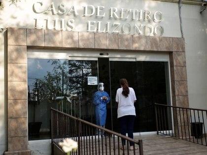 """Un trabajador médico da información a una mujer sobre un pariente afuera del asilo de ancianos """"Casa de Retiro Luis Elizondo"""", donde hay un brote de coronavirus, en Guadalupe, en las afueras de Monterrey, (Foto: REUTERS/Daniel Becerril)"""