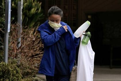 FILE PHOTO: A worker removes her mask upon leaving the Life Care Center of Kirkland, the long-term care facility linked to several confirmed coronavirus cases in the state, in Kirkland, Washington, U.S. March 6, 2020.  REUTERS/David Ryder/File Photo