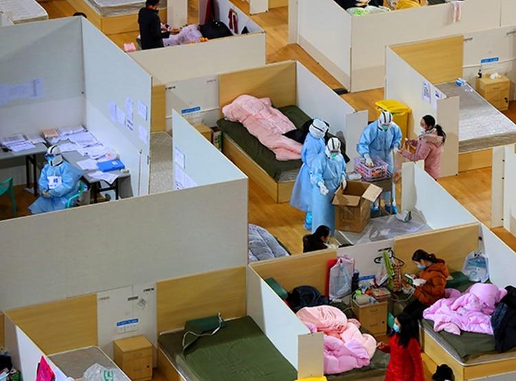 Personal médico vestido con trajes protectores distribuye comida en un estadio deportivo que se ha convertido en un hospital improvisado para tratar a los pacientes del nuevo coronavirus, en Wuhan, el 2 de marzo de 2020 (China Daily vía Reuters)