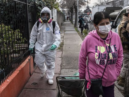 A municipal worker cleans and disinfects the streets of San Miguel neighbourhood in Santiago, on July 7, 2020 amid the new coronavirus pandemic. - Chile surpassed 300,000 coronavirus infections on Tuesday, adding 2,462 new cases in the last 24 hours and 50 deaths, and confirming a descending trend over the last 23 days that has led authorities to begin planning the easing of the confinement. (Photo by Martin BERNETTI / AFP)